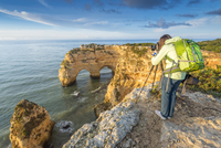 Praia de Marinha, Caramujeira, Lagoa, Algarve, Portugal. Woman photographing the coastal rock formations at sunrise. 20088066670| 写真素材・ストックフォト・画像・イラスト素材|アマナイメージズ