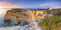 Praia de Marinha, Caramujeira, Lagoa, Algarve, Portugal. Panoramic view of a woman photographing the sunrise from above the clif 20088066672| 写真素材・ストックフォト・画像・イラスト素材|アマナイメージズ
