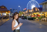 South East Asia, Thailand, Bangkok, Bang Kho Laem district, a young Thai woman checks her smartphone in front of the Asiatique t 20088078972| 写真素材・ストックフォト・画像・イラスト素材|アマナイメージズ