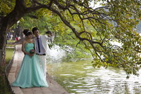 Vietnam, Ha Noi, Hoan Kiem Lake. A young couple pose for a photograph in their wedding finery. 20088091890| 写真素材・ストックフォト・画像・イラスト素材|アマナイメージズ