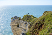 France, Normandy (Normandie), Seine-Maritime department, Etretat. A womand stands on the edge of white cliffs overlooking the En