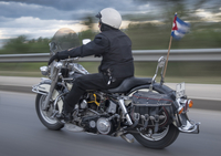 Man riding a Harley Davidson motorcycle at speed with a Cuban pennant blowing in the wind. 20089001340| 写真素材・ストックフォト・画像・イラスト素材|アマナイメージズ