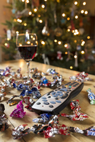 TV remote control surrounded by sweet wrappers and a glass of red wine at Christmas. 20089004822| 写真素材・ストックフォト・画像・イラスト素材|アマナイメージズ