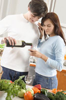 Young couple standing in kitchen, man pouring wine 22199047991| 写真素材・ストックフォト・画像・イラスト素材|アマナイメージズ