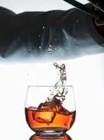 Barman dropping ice cube into cocktail glass from ice tongs 22199071995| 写真素材・ストックフォト・画像・イラスト素材|アマナイメージズ