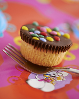 A cupcake decorated with chocolate glaze and colourful chocolate beans 22199076002| 写真素材・ストックフォト・画像・イラスト素材|アマナイメージズ