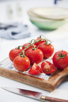 Tomatoes on a board with a knife 22199080351| 写真素材・ストックフォト・画像・イラスト素材|アマナイメージズ