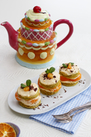 Individual mandarin layer cakes with quark cream icing, in front of a teapot 22199081521| 写真素材・ストックフォト・画像・イラスト素材|アマナイメージズ