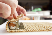 Maki sushi being rolled up using a bamboo mat 22199081598| 写真素材・ストックフォト・画像・イラスト素材|アマナイメージズ