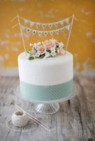 A wedding cake with sugar flowers, a ribbon and a 'Just Married' bunting decoration 22199082481| 写真素材・ストックフォト・画像・イラスト素材|アマナイメージズ