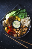 A vegan Buddha bowl with mie noodles, mango, pineapple, bok choy, grilled peppers, tofu and coconut curry sauce (Asia) 22199083270| 写真素材・ストックフォト・画像・イラスト素材|アマナイメージズ