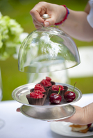 Cherry sorbet in chocolate cups under a glass dome