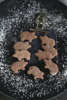 Pig-shaped gluten-free biscuits on a black plate surrounded by a dusting of icing sugar 22199091688| 写真素材・ストックフォト・画像・イラスト素材|アマナイメージズ