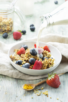 Granola with turmeric and fruit in a bowl of milk 22199093545| 写真素材・ストックフォト・画像・イラスト素材|アマナイメージズ