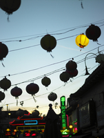 Oriental lanterns hanging over street with neon lights in Chinatown, California, USA.