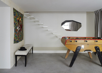 Games area with floating staircase, irregular shaped mirror and football table in French residential home. 25937008149| 写真素材・ストックフォト・画像・イラスト素材|アマナイメージズ