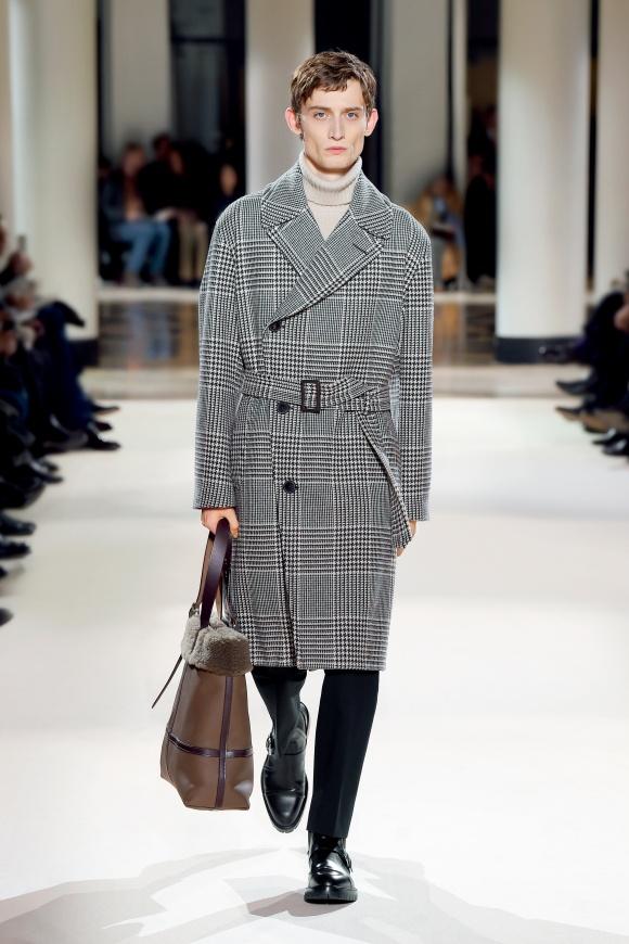 永遠性のあるコート姿で、 旬の羊革のトートを持つ。