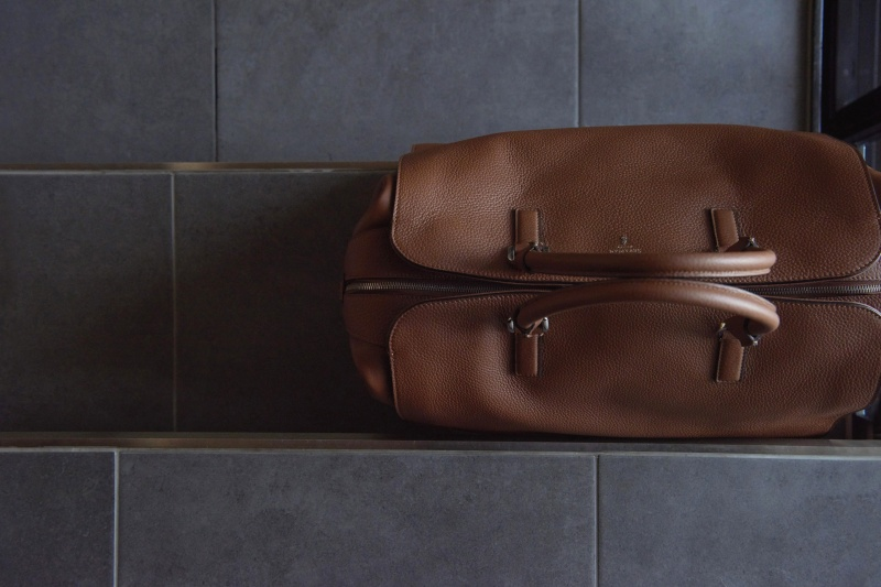 大型のダッフルバッグが、スタイリッシュな旅へと誘う。