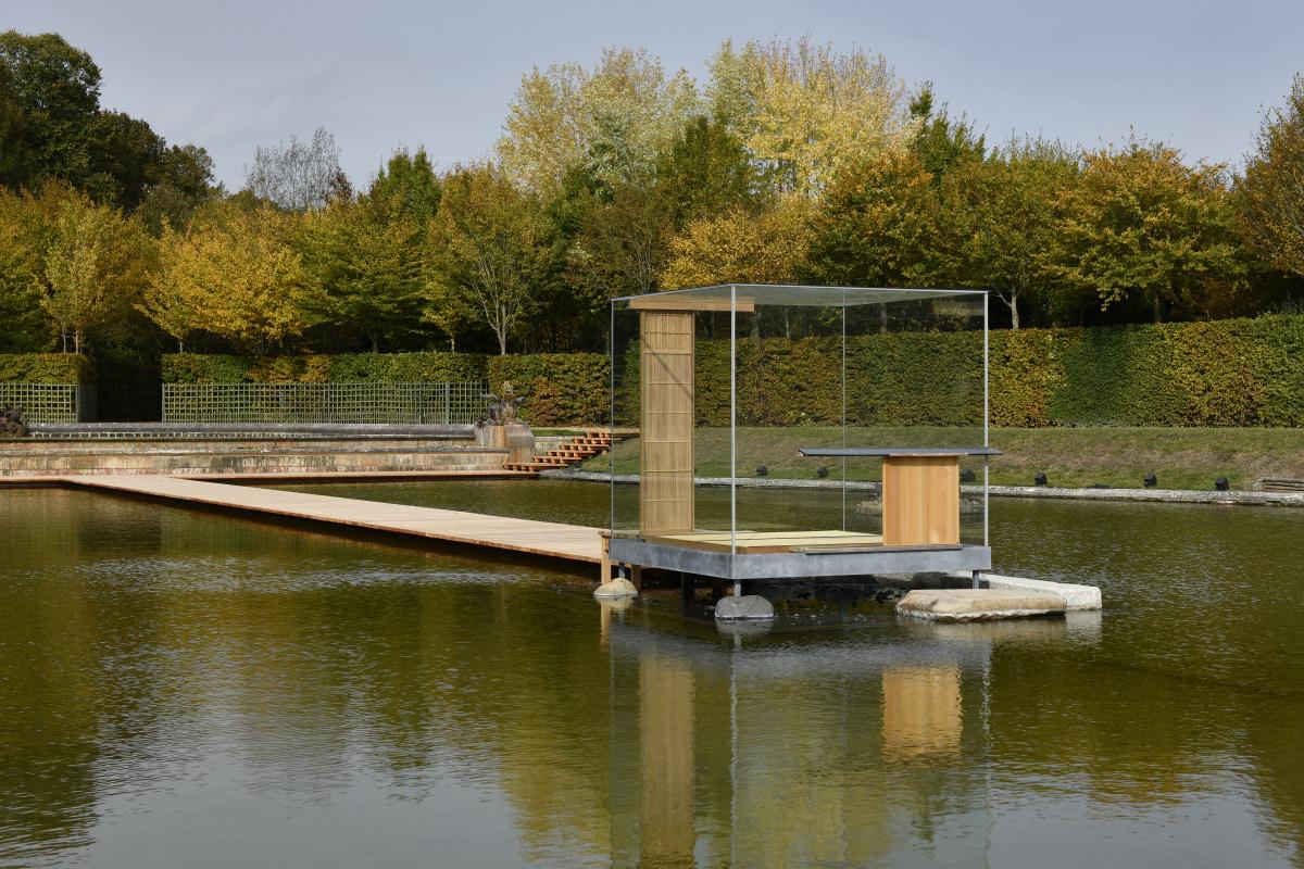 庭園の池に、ガラスの茶室が浮かぶ。