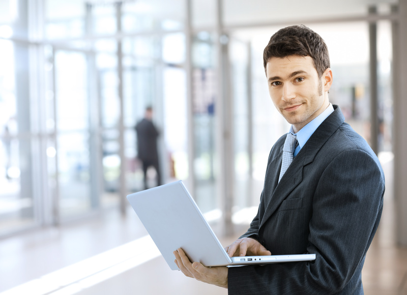 Young smiling businessman using laptop on corporate location, indoor.