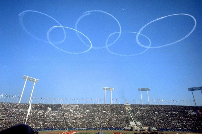 東京オリンピックの開会式当日、会場上空に描かれた五輪マーク=1964年10月10日、東京都新宿区の国立競技場