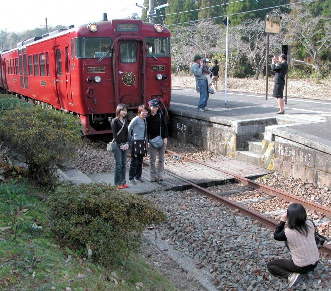 肥薩線を走る「いさぶろう号」をバックに記念写真を撮る乗客たち=2005年12月10日:出典・朝日新聞