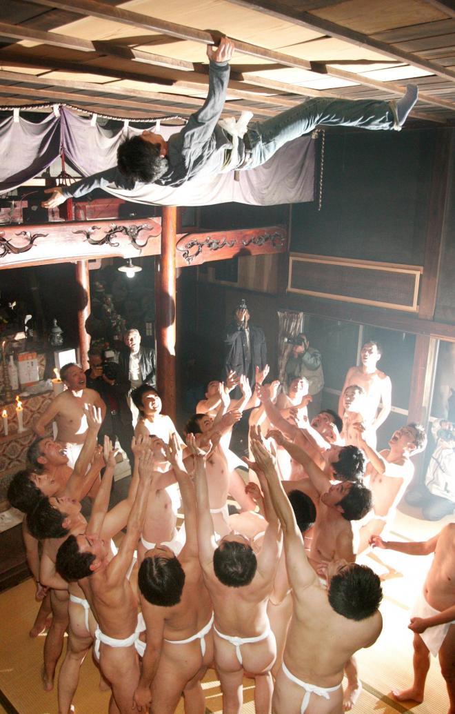 【裸胴上げ】新潟県能生(のう)町の藤崎観音堂で17日夜、約300年前から伝わる「裸胴上げ」があった。さらしのふんどしをしめた約25人の男たちが、隠れている厄年の男性を見つけて大の字に担ぎ上げ「サッシャゲー、サッシャゲー」のかけ声でお堂中を練り歩く。最後は天井めがけて高々と放り投げる。天井まで届く人が現れると祭りは最高潮に達し、歓声が上がった=2005年1月17日:出典・朝日新聞