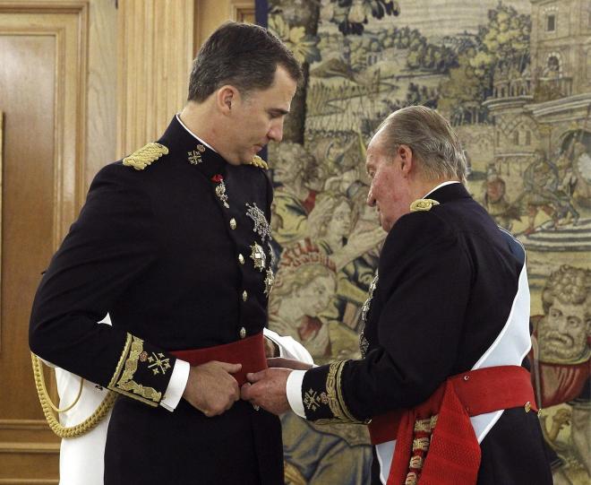 フアン・カルロス1世(右)から、赤いベルトを巻いてもらう新国王のフェリペ6世