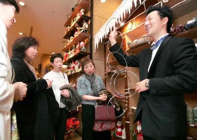 ホテルを訪れた人たちを楽しませる手品師=2005年12月20日、名古屋市中区