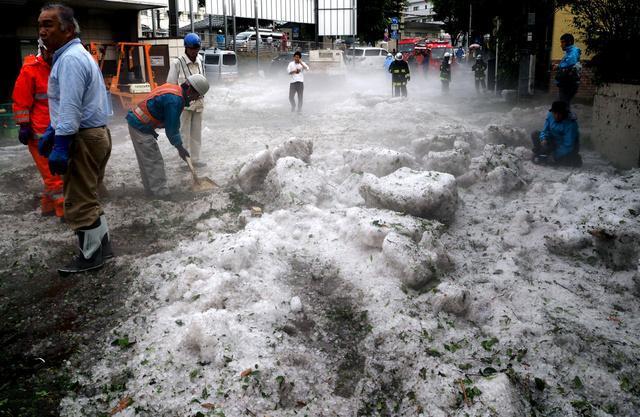 道路に降り積もったひょうの後片付けをする人たち=24日午後5時37分、東京都調布市、山本裕之撮影