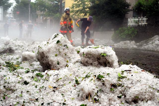 道路に積もったひょうを脇にかく市民や消防隊員ら=24日午後6時すぎ、東京都調布市東つつじケ丘1丁目、高橋友佳理撮影