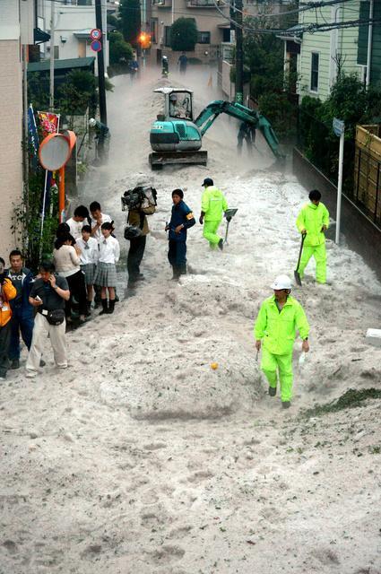降り積もったひょうの後片付けに追われる住民ら=24日午後7時1分、東京都三鷹市中原1丁目、小玉重隆撮影
