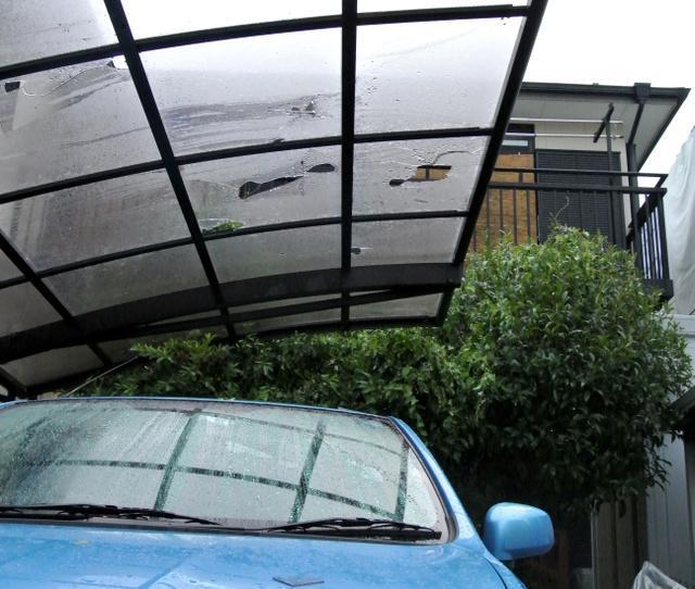 ひょうで穴が開いたガレージの屋根=24日午後6時46分、東京都三鷹市中原2丁目、仙波理撮影
