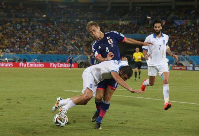 後半、浮き球の奪い合いでギリシャ・マニアティスに阻まれる本田(4)=上田潤撮影