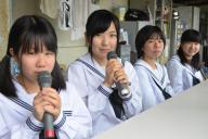 学校グラウンドの放送席でマイクを持つ梶原さん(左から2人目)ら柳井高校野球部のマネジャー