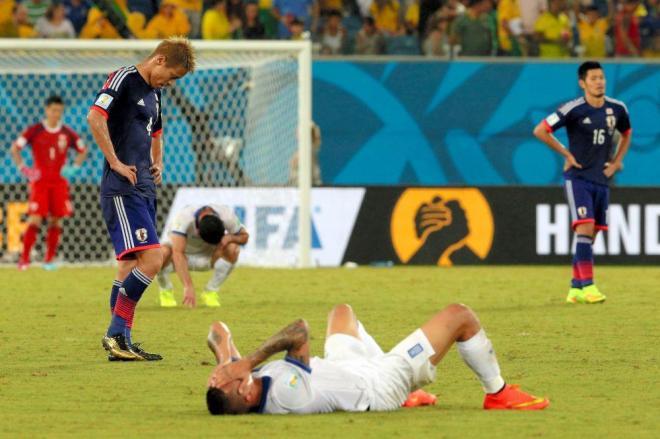 試合終了後、うなだれる本田(4)と倒れ込んだギリシャ選手=上田潤撮影