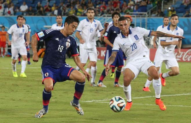 後半12分に途中交代で出場した香川(10)が、ギリシャ・ホレバス(20)とボールを奪い合う=上田潤撮影
