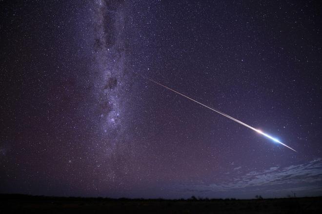 南天の天の川の前を右下から上方へ横切った「はやぶさ」と回収カプセル=日本時間2010年6月13日、豪州南部グレンダンボ近郊