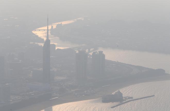 かすんで視界が悪くなった福岡市内。中央左は福岡タワー=2013年12月6日、朝日新聞社ヘリから