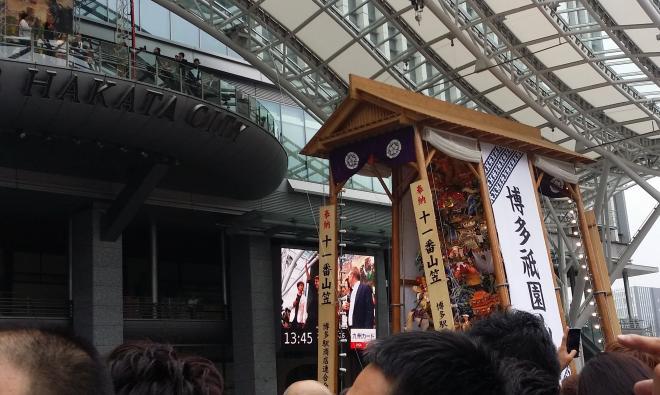 トム(左上)がかすむぐらいの山車と人だかり=博多駅前