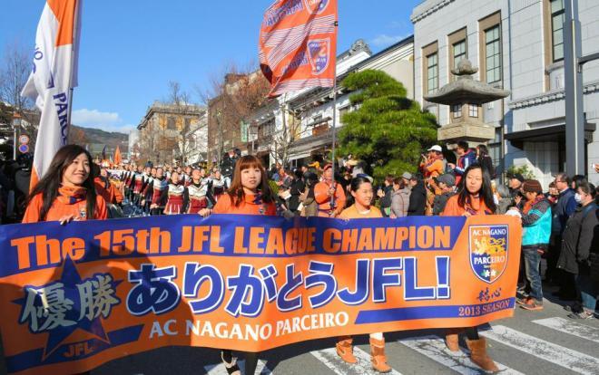 横断幕を掲げてパレードするAC長野パルセイロのスタッフや選手ら
