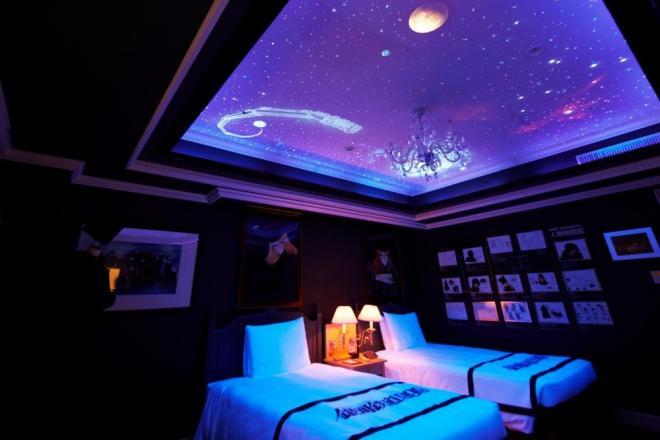 ブラックライトで銀河を走る999号が浮かび上がるベッドルーム