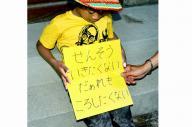 「せんそういきたくない」「だぁれもころしたくない」。そう書いたプラカードを持ってデモ行進に参加した子ども=2014年7月1日、名古屋市西区