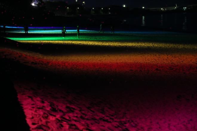 虹色に照らし出された浜辺=30日午後8時9分、山口県光市の虹ケ浜海水浴場、金子淳撮影