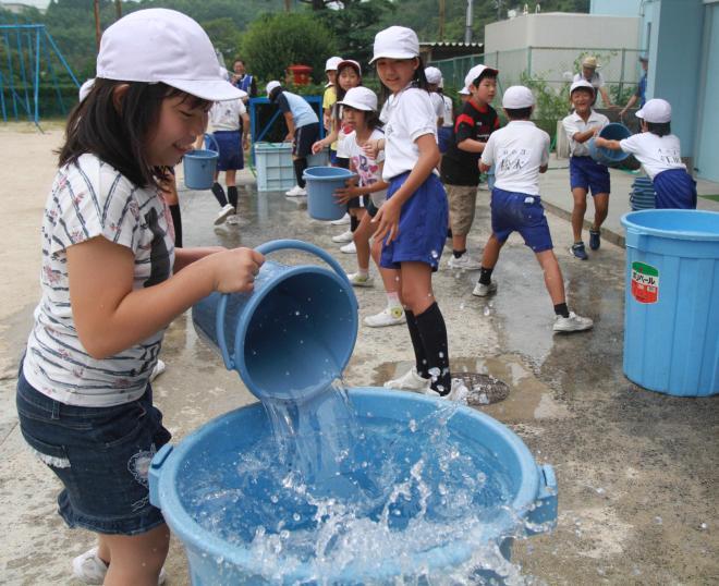 バケツリレーの練習をする子どもたち=山口県下松市の久保小学校