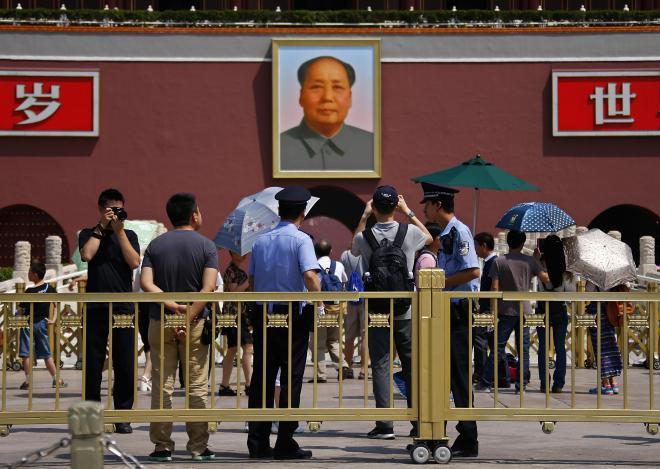 北京の天安門広場で、写真撮影する観光客を見張る警察官=2014年6月3日