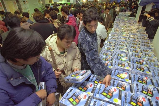 長い時間並んだ後店内に入り、発売された「ウィンドウズ95」の日本語版を買い求める人たち=1995年11月23日午前0時すぎ、東京・秋葉原で