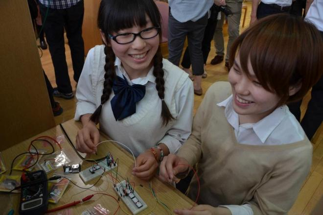 閲覧机の下にセンサーを取り付け、図書館アプリの稼働テストをする鯖江市役所JK課員