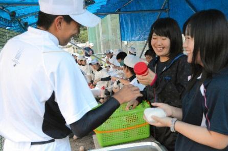 特大のおにぎりを部員に手渡す登米高マネジャーの佐藤さん(右)と阿部さん=登米市