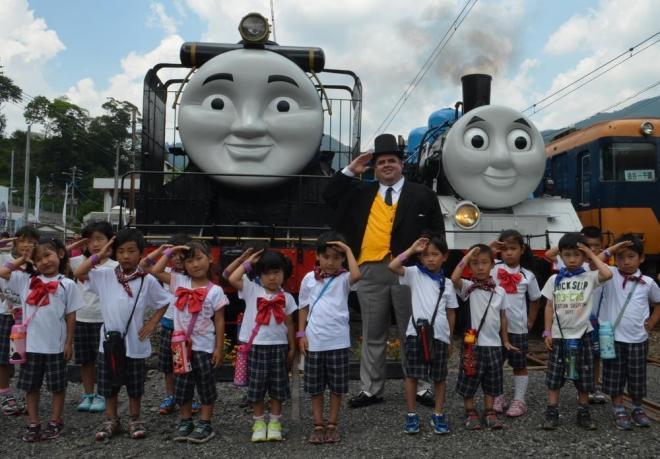 トーマス号(右)と、仲間のヒロ号(左)の前で、アニメに出てくる鉄道局長トップハム・ハット卿に扮した男性と一緒に敬礼する園児たち